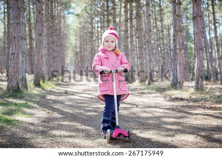 happy toddler girl on a scooter in a forest - stock photo