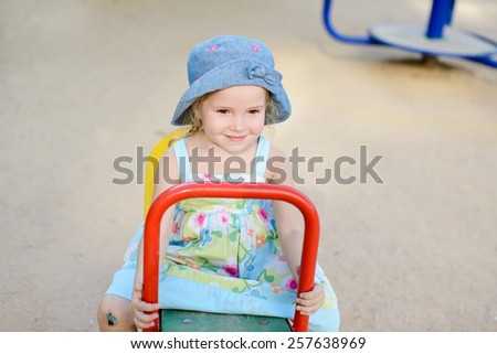 happy toddler girl on the playground in summer - stock photo
