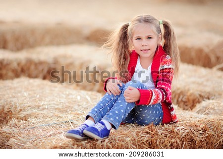 Happy toddler girl picking a pumpkin for Halloween on Pumpkin Putch - stock photo