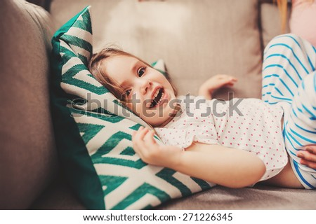 happy toddler girl playing at home on the sofa - stock photo