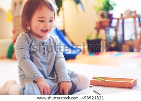 Happy toddler girl playing in her house