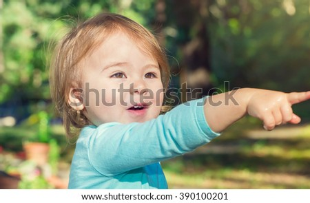 Happy toddler girl playing outside on a bright summer day