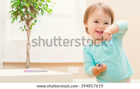 Happy toddler girl playing with chalk in her in house - stock photo