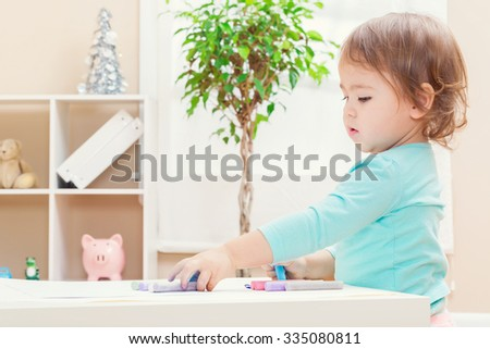 Happy toddler girl playing with chalk inside her house - stock photo