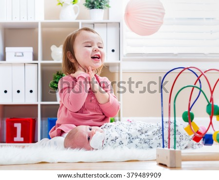 Happy toddler girl playing with her newborn sister