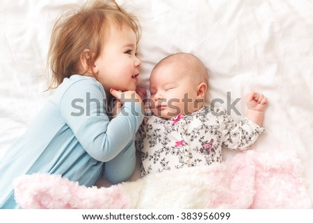 Happy toddler girl playing with her newborn sister - stock photo