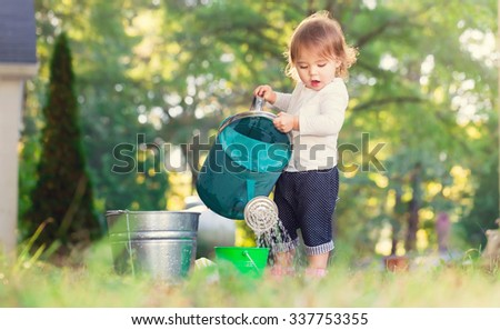 Happy toddler girl playing with watering cans outside  - stock photo