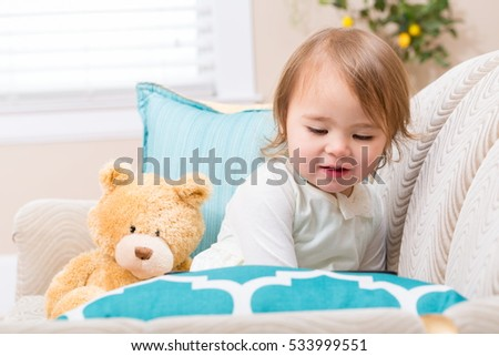 Happy toddler girl sitting with her teddy bear on her couch