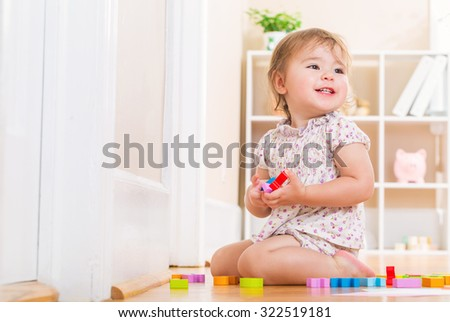 Happy toddler girl smiling and playing with her wooden toy blocks in her house - stock photo