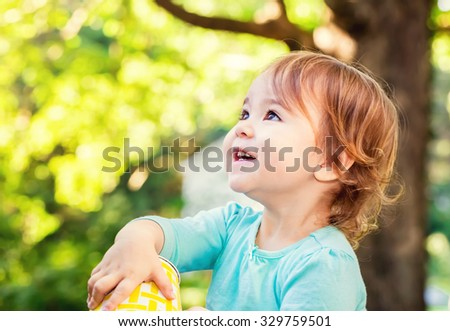 Happy toddler girl smiling outside on a sunny afternoon - stock photo