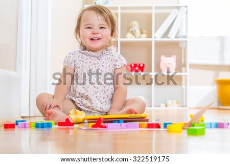 Happy toddler girl smiling while playing with her toy blocks  - stock photo