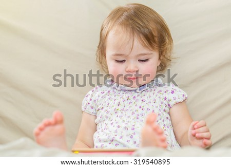 Happy toddler girl watching cartoons on her tablet computer - stock photo
