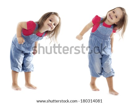 Happy toddler girl wearing jeans jumpsuit is having a great time dancing in the studio. Isolated on white.  - stock photo