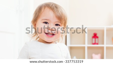 Happy toddler girl with a big smile in her house - stock photo