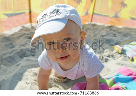 Happy toddler having fun on the beach