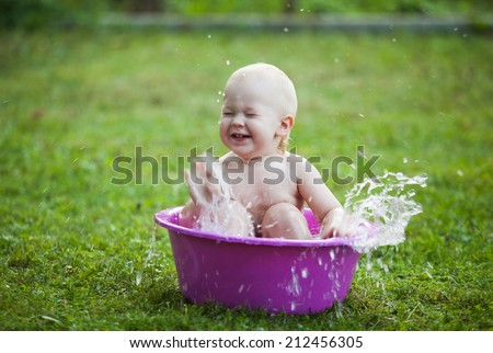 Happy toddler in a washbowl on the grass at the yard - stock photo