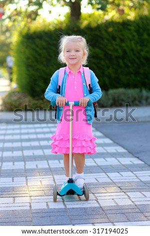 Happy toddler kid with small backpack going to school. Preschooler girl safely riding scooter crossing road on zebra pad. Active little child wearing bright pink dress enjoying sunny day outdoors. - stock photo