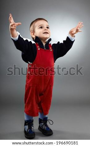 Happy toddler over gray background, full length shot - stock photo