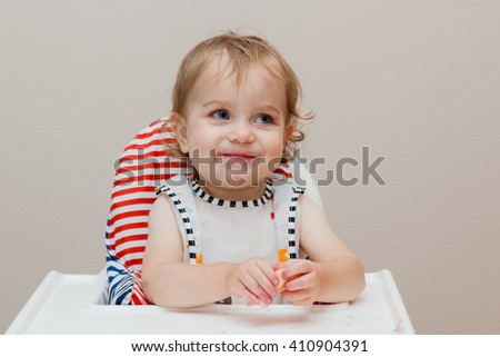 Happy toddler sitting in highchair and eating fruits. Baby learning to eat and has pieces of food on face. - stock photo