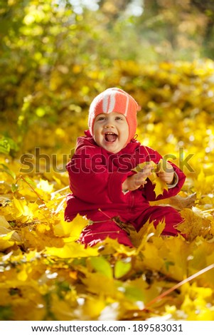 Happy toddler sitting on maple leaves in autumn park