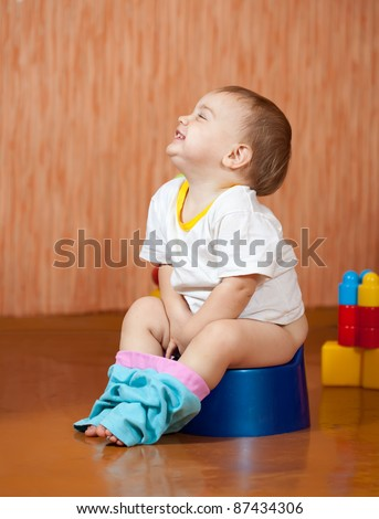 Happy toddler sitting on potty in home interior - stock photo
