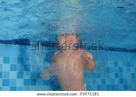 Happy toddler swimming in the pool and smiling - stock photo