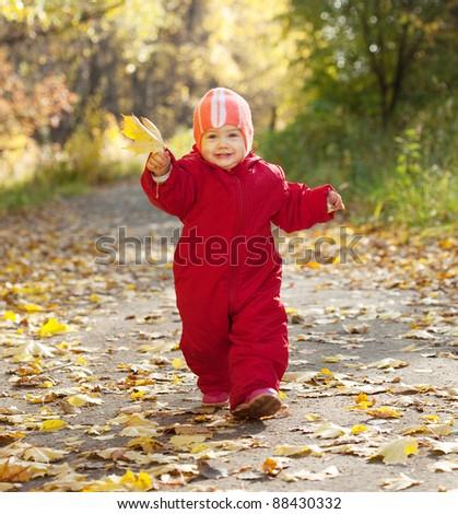 Happy toddler walking  in autumn park - stock photo
