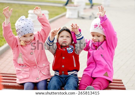 happy toddlers in the park with hands up (selective focus) - stock photo