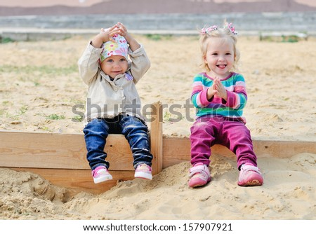 happy toddlers sitting in sand - stock photo