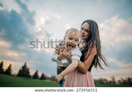 Happy together. Beautiful young mother and her son having fun at cloudy field. Wide angle photo - stock photo