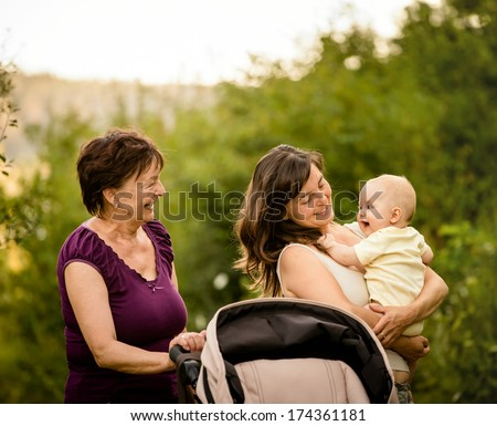 Happy together - grandmother with her daughter and her granddaughter outdoor in nature - stock photo