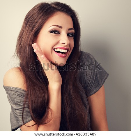 Happy toothy laughing brunette young woman with hand near face. Toned closeup portrait - stock photo