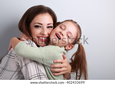 Happy toothy smiling mother cuddling emotional kid girl with closed eyes in studio on blue background.