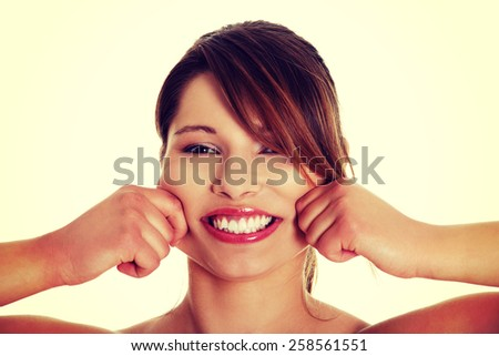 Happy toothy smiling woman pulling her cheeks. - stock photo