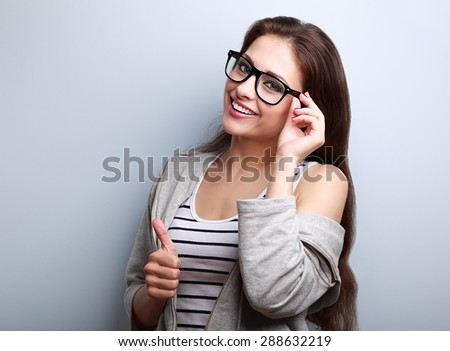Happy toothy smiling young woman in glasses showing thumb up on blue background with empty copy space - stock photo