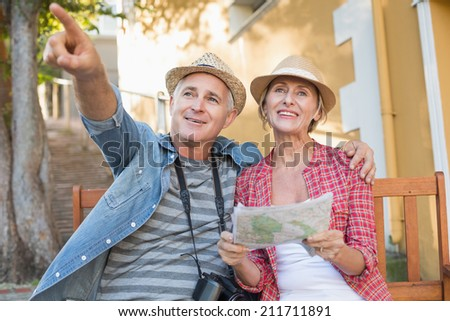 Happy tourist couple looking at map on a bench in the city on a sunny day - stock photo