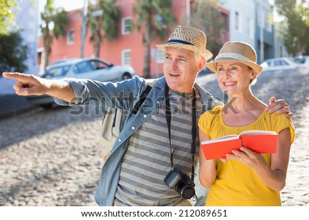 Happy tourist couple using guide book in the city on a sunny day - stock photo