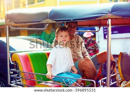 happy tourist family travel through the asian city on tuk-tuk taxi - stock photo