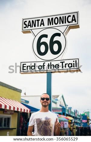 Happy Tourist in Historic Route 66 sign at Santa Monica California - stock photo