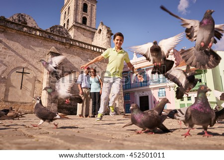 Happy tourist on holidays during vacation trip. Hispanic people traveling in Havana, Cuba. Grandpa and grandson feeding birds, with child running chasing pigeons - stock photo