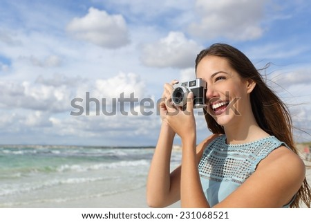 Happy tourist photographer girl taking photo in holidays with a cloudy sky and the sea in the background - stock photo