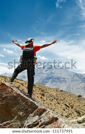 happy tourist traveller hiker reached mountain top in Himalayas - stock photo