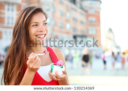 Happy tourist woman eating Ice cream in Quebec City in front of chateau frontenac in Quebec City, Quebec Canada. Smiling joyful mixed race Asian Caucasian girl enjoying holiday travel in summer dress - stock photo