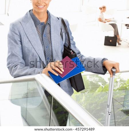 happy tourist woman holding passport - stock photo