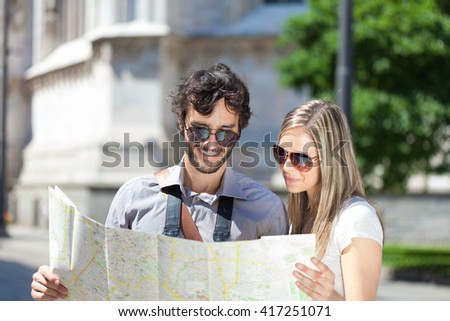 Happy tourists couple holding a city map - stock photo