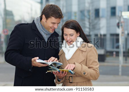 Happy tourists on holiday with tour guide and city map - stock photo
