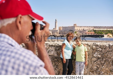 Happy tourists on holidays. Hispanic people traveling in Havana, Cuba. Grandfather, grandmother and grandchild during summer travel, with senior man taking photos with camera