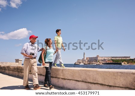 Happy tourists on holidays in Havana, Cuba. Hispanic family with grandpa, grandma and grandson traveling and walking together on the Malecon - stock photo