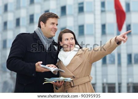 Happy tourists on sightseeing trip with tour guide and city map - stock photo