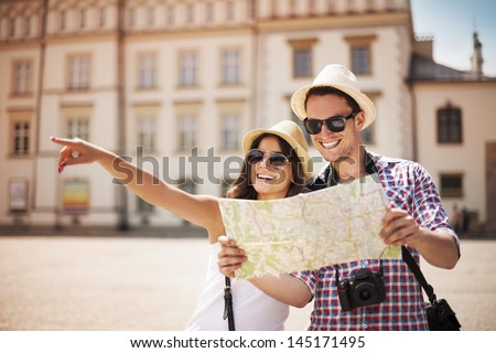 Happy tourists sightseeing city with map - stock photo